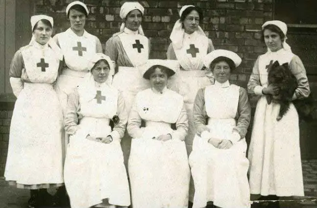 Eight nurses wearing old uniforms in ancient times