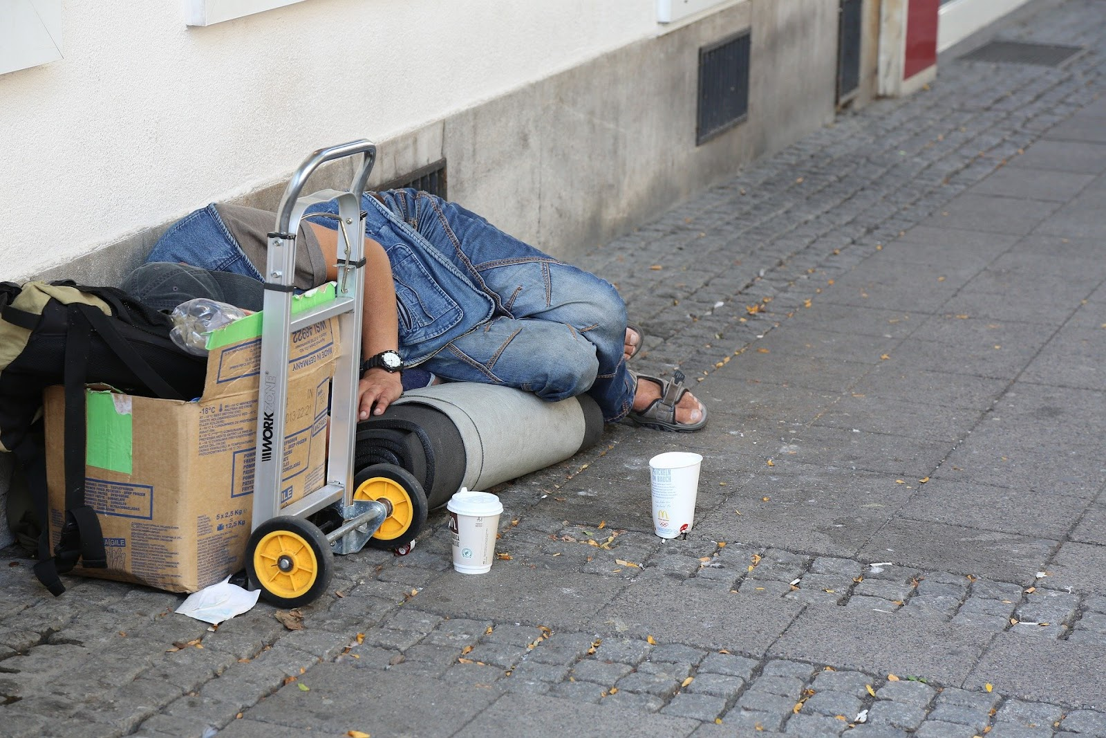 A homeless individual sleeps on a sidewalk with a box and empty cups.