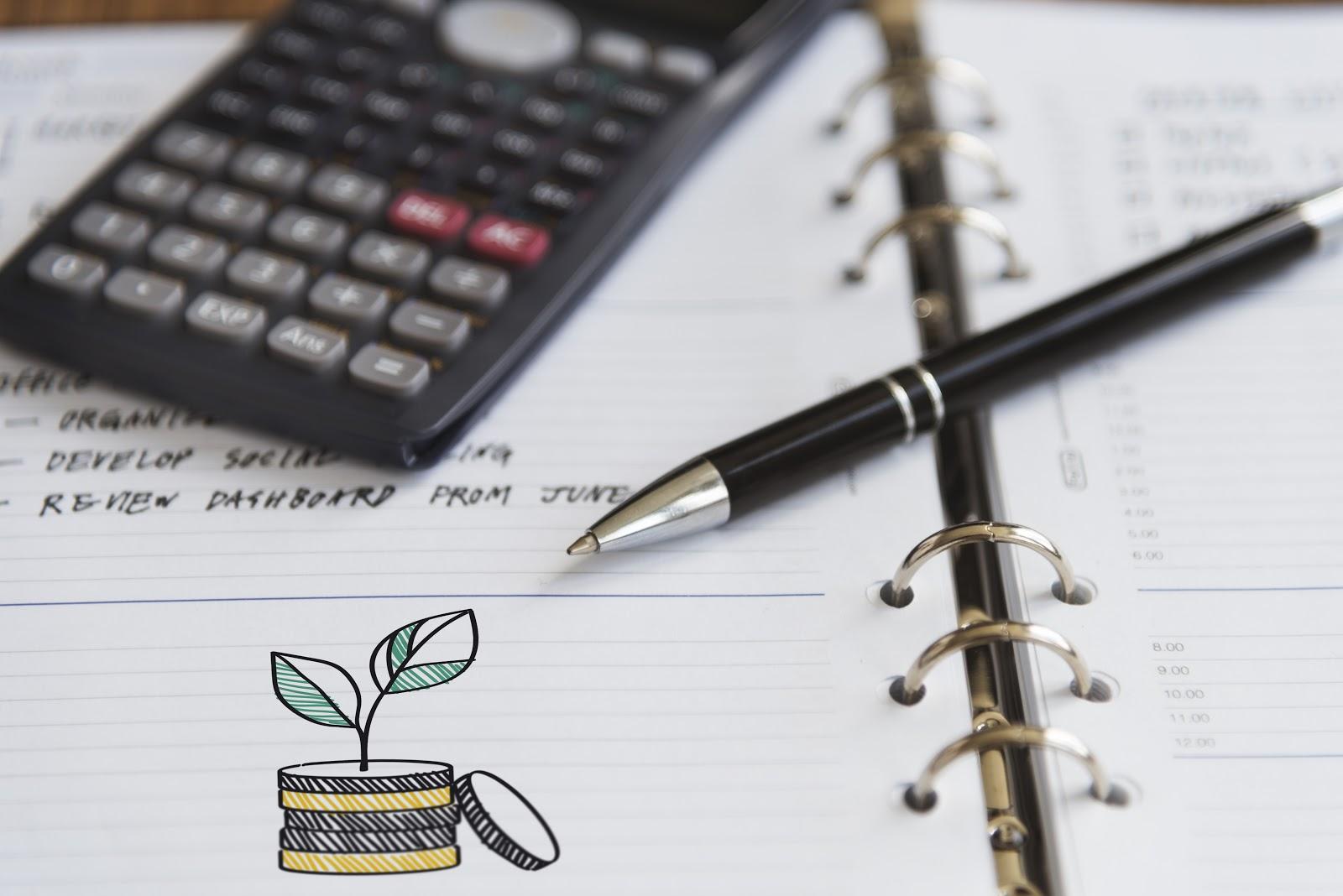 Um caderno com uma calculadora e uma caneta em cima.