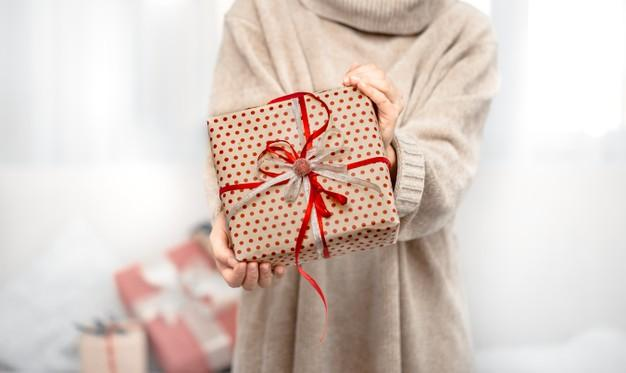 A woman is holding a beautiful christmas gifts. Free Photo