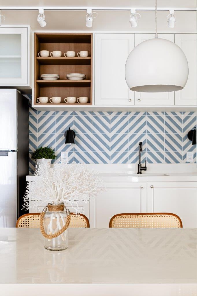 Cozinha com mesa branca e cadeiras de palha, armários brancos, luminária pendente e azulejos geométricos azul e branco.