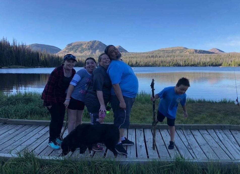 A group of people posing for a photo with a dog  Description automatically generated with medium confidence