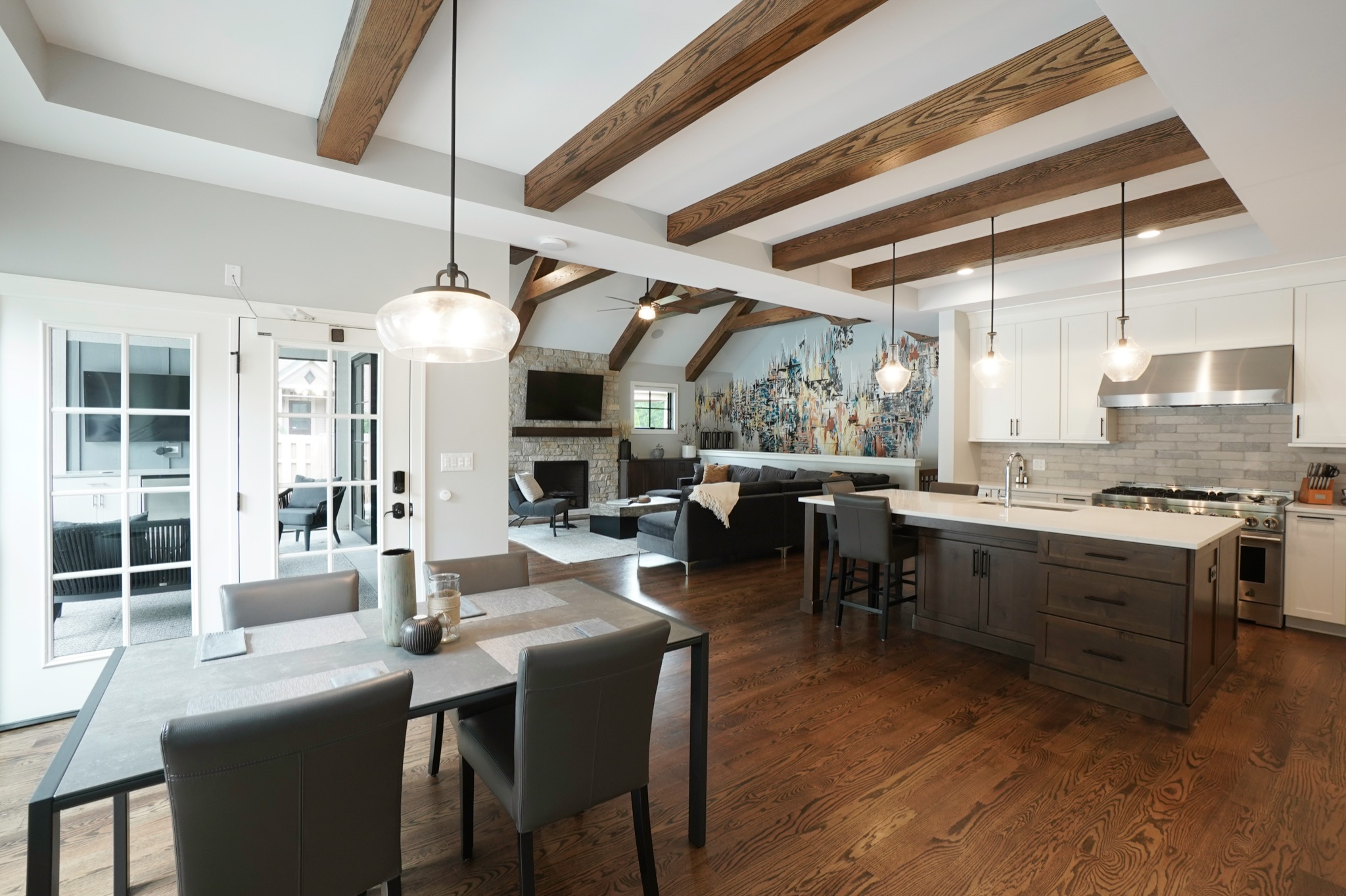 Open kitchen and living room space with exposed natural wood beamed ceilings, dark wood cabinets and a living room with a focal mural wall