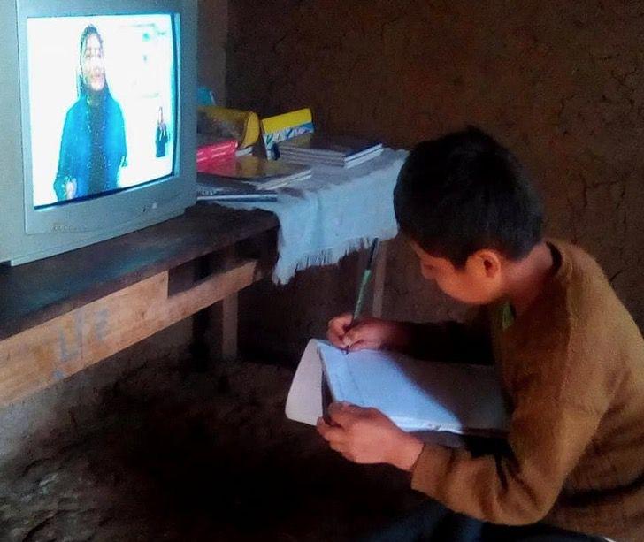 Niño tomando clases a distancia por medio de una televisión