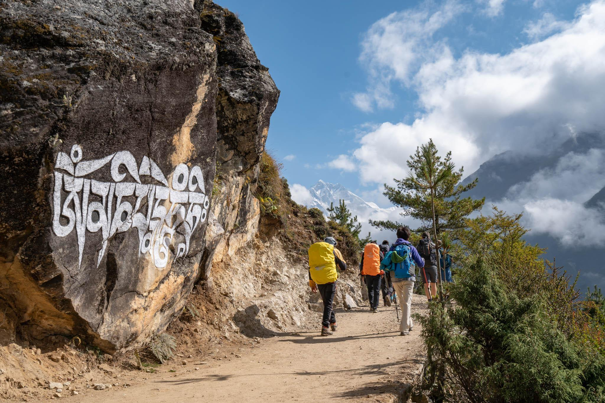 A group of walkers passing some Nepalese writing on a rock