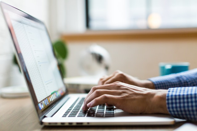 A Virtual assistant typing his blog post on a laptop