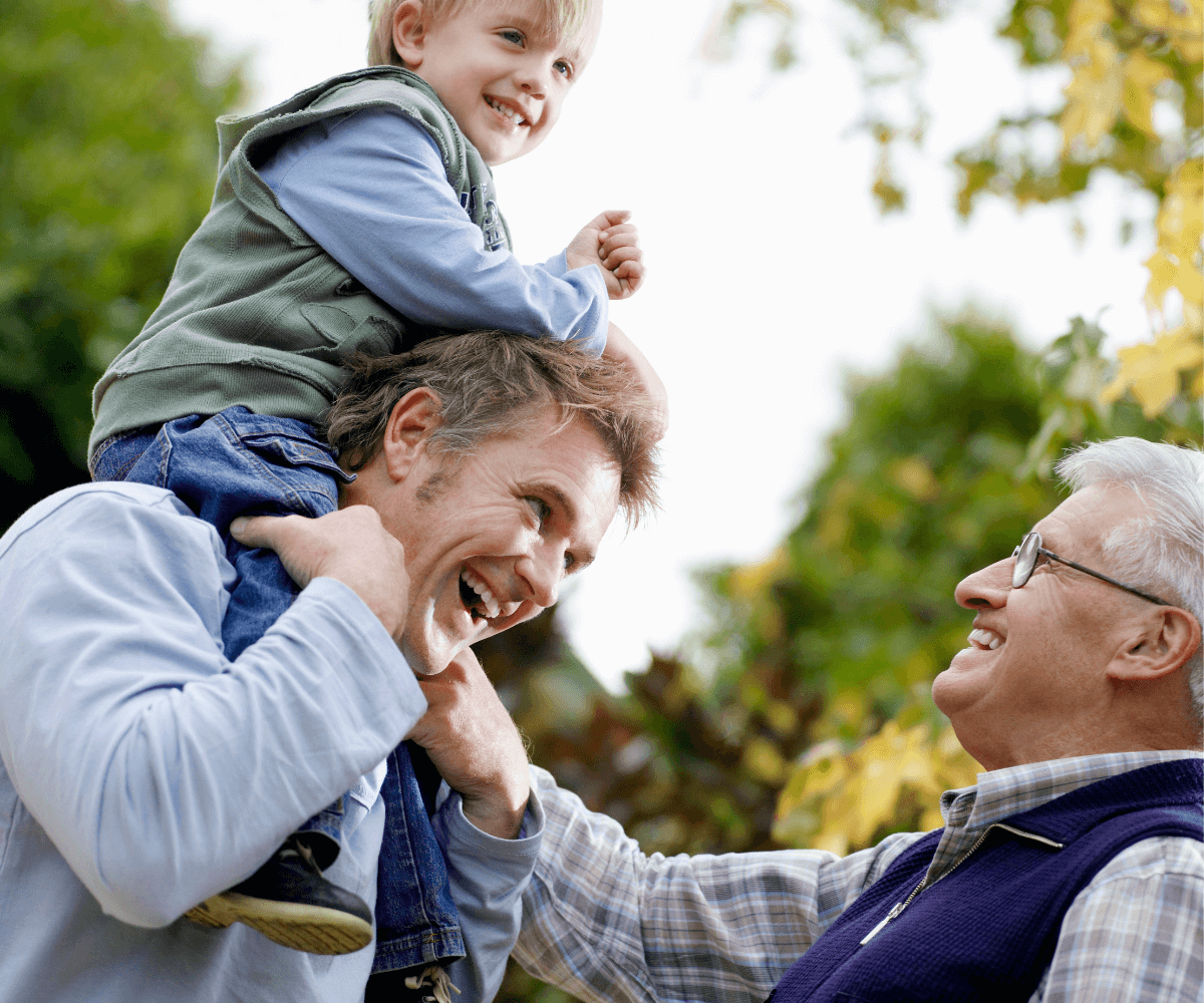 Elderly man with glasses and white hair on the bottom right corner looking at his middle aged son with toddler on his shoulders. 3 generations of men and fathers.