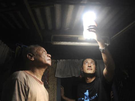 Deux hommes dans un bidonville regardant une bouteille brillante servant de lumière low-tech qui ressort du toit.