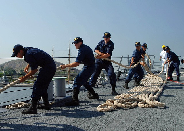 Sailors pulling rope on boat