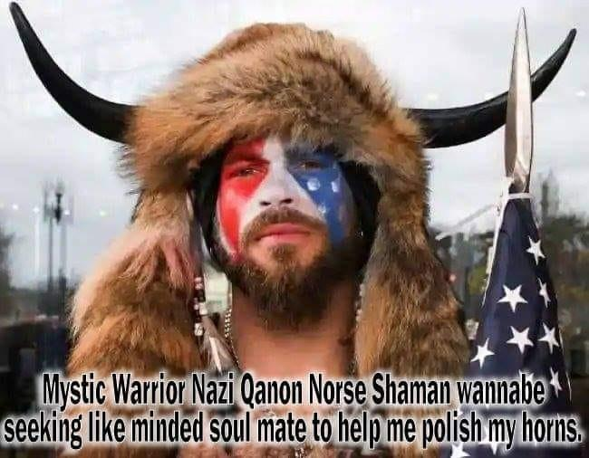 "Billedet indeholder sandsynligvis: 1 person, tekst, der siger ""Mystic Warrior Nazi Qanon Norse Shaman wannabe seeking like minded soul mate to help me polish my horns."""