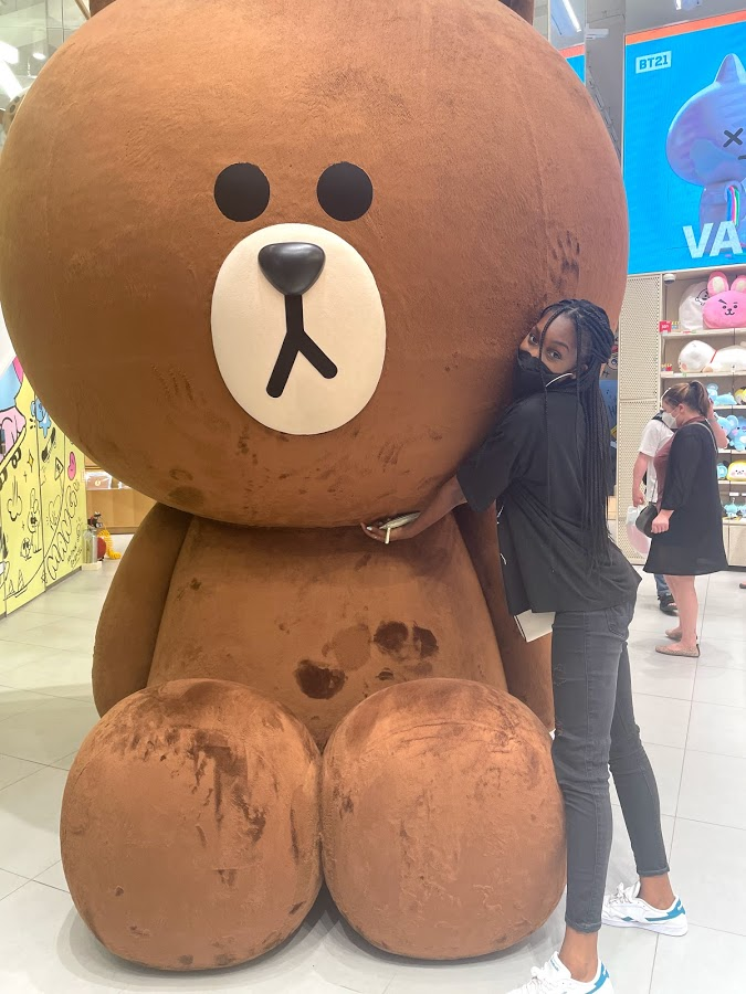 A person standing next to a giant stuffed animal  Description automatically generated with low confidence
