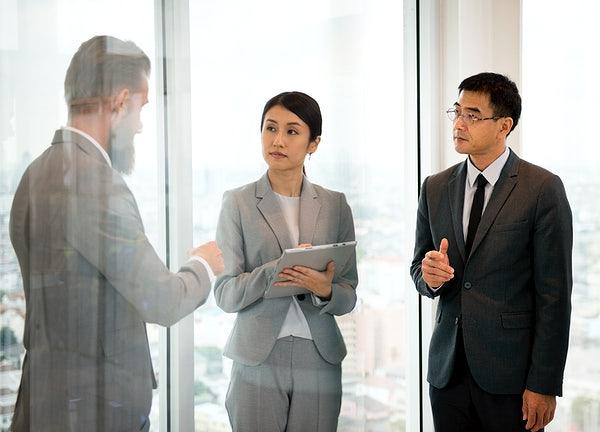 Duas pessoas observando uma terceira falar.
