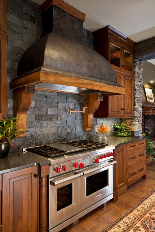 rustic kitchen with dark brick stone backsplash, stained wood cabinets, matching wood floors and large range hood oven