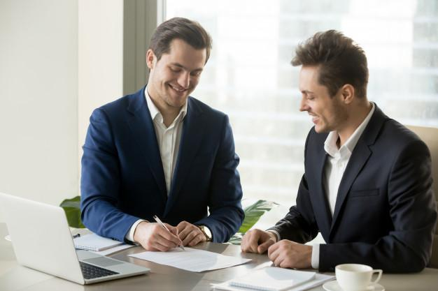 Handsome businessman signing contract with partner Free Photo