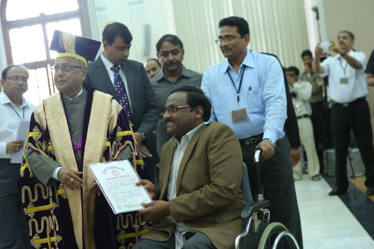 The President of India, Pranab Mukherjee, presents Saibaba with his doctoral degree at the 90th convocation of Delhi University on March 19, 2013 .