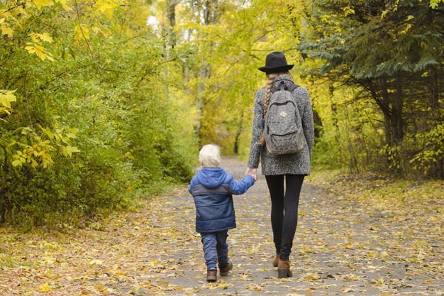 Mamá e hijo están caminando en el bosque de otoño Foto Premium