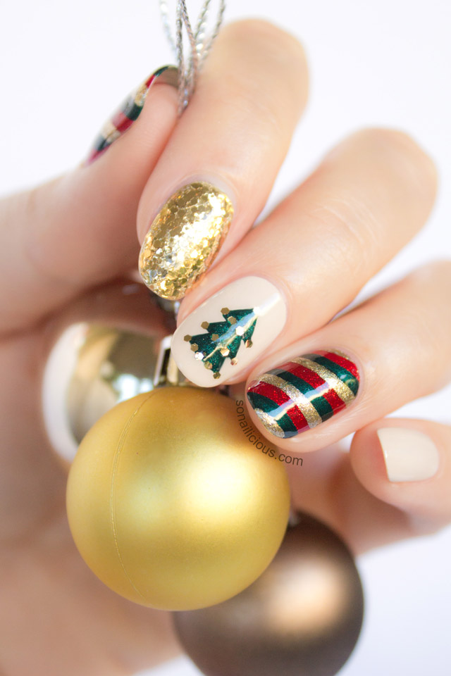 Nails with assorted Christmas nail art, including Christmas tree, gold glitter & red, green & gold stripes