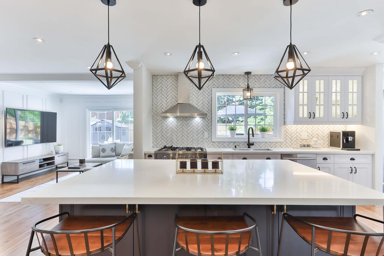 Geometric pendant lights placed above the kitchen island along with other stainless steel luxury elements in the background.