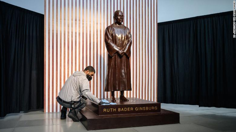 A janitor cleans the statue of late US Supreme Court Jusice Ruth Bader Ginsburg that went on display in Brooklyn.