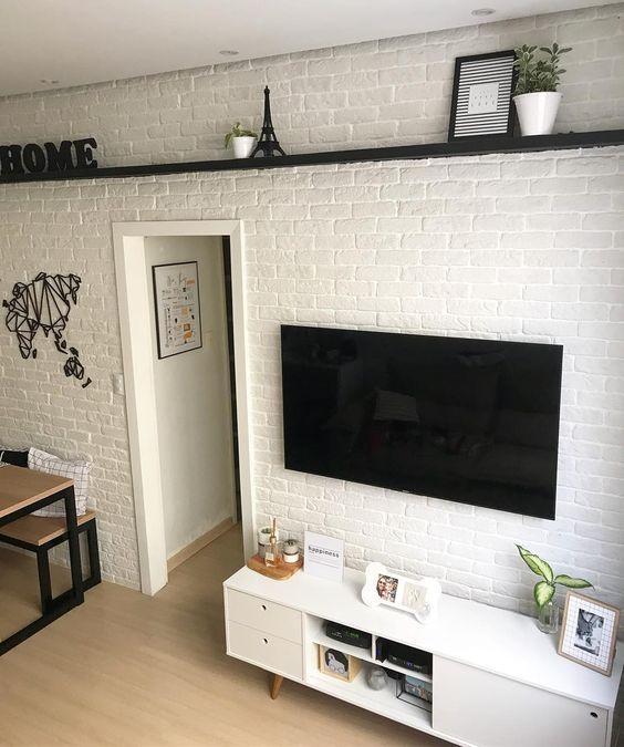 Parede de sala de estar com tijolinhos aparentes na cor branco. Prateleira preta com objetos, armário baixo com pés de palito e piso de madeira.