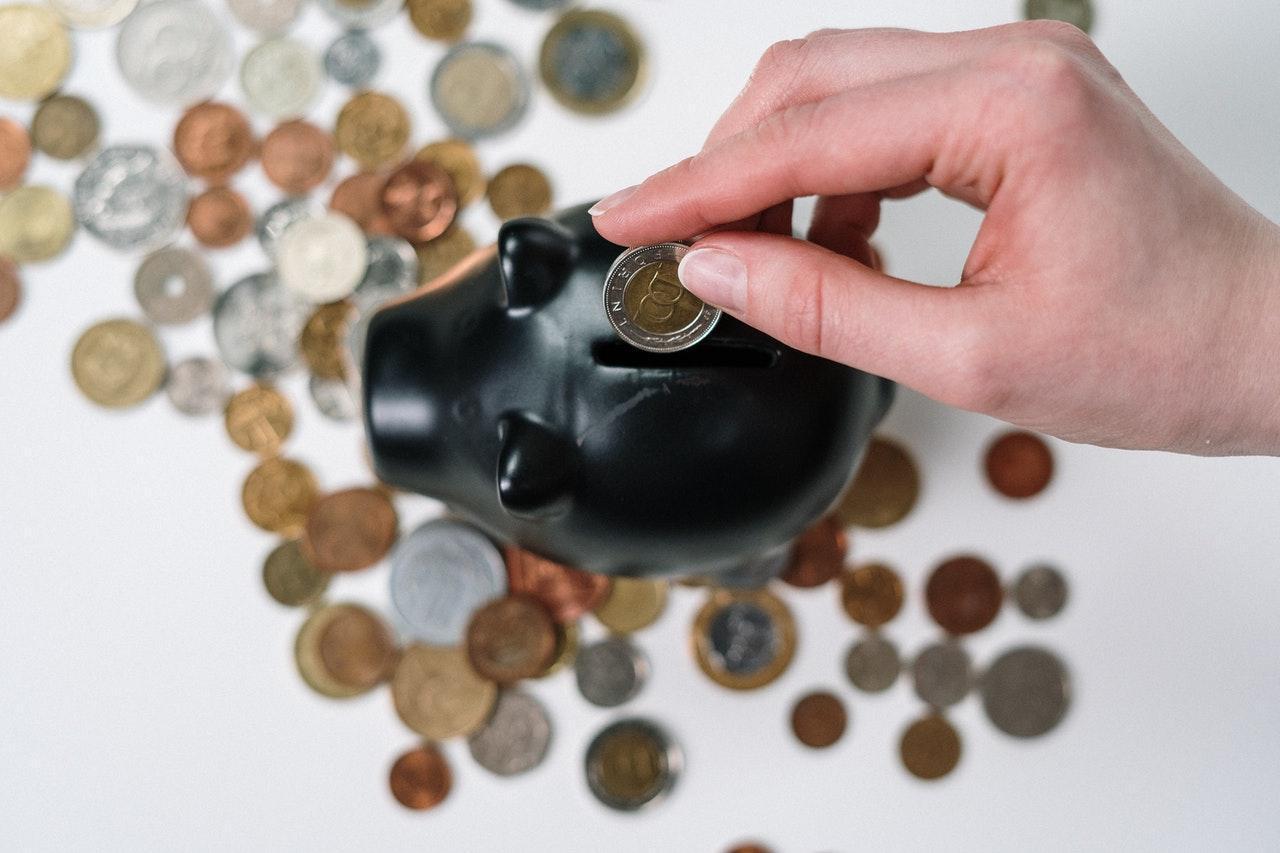 Tirelire et une personne qui depose de l'argent dedans