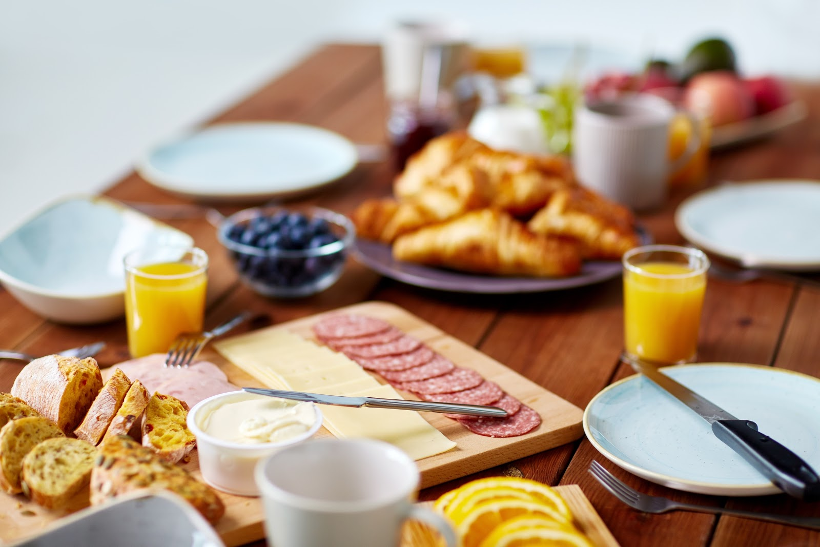 Mesa completa de coffee break: com sucos, pães, frios e frutas