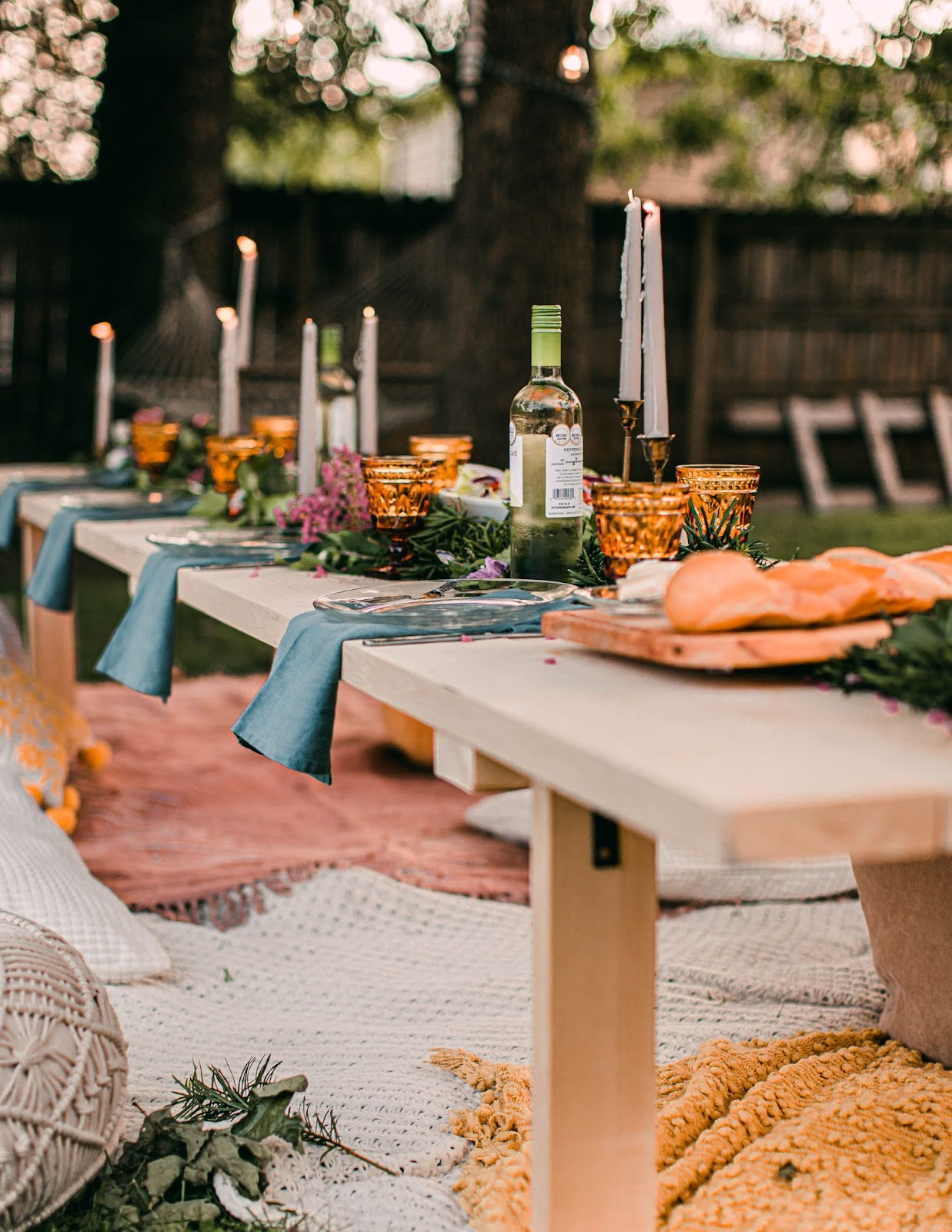 A table with food, wine and candles in a garden