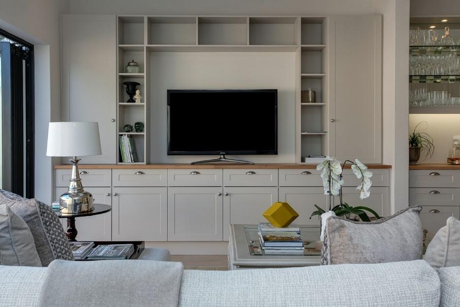 A living room with a TV on a white cabinet surrounded by shelves.