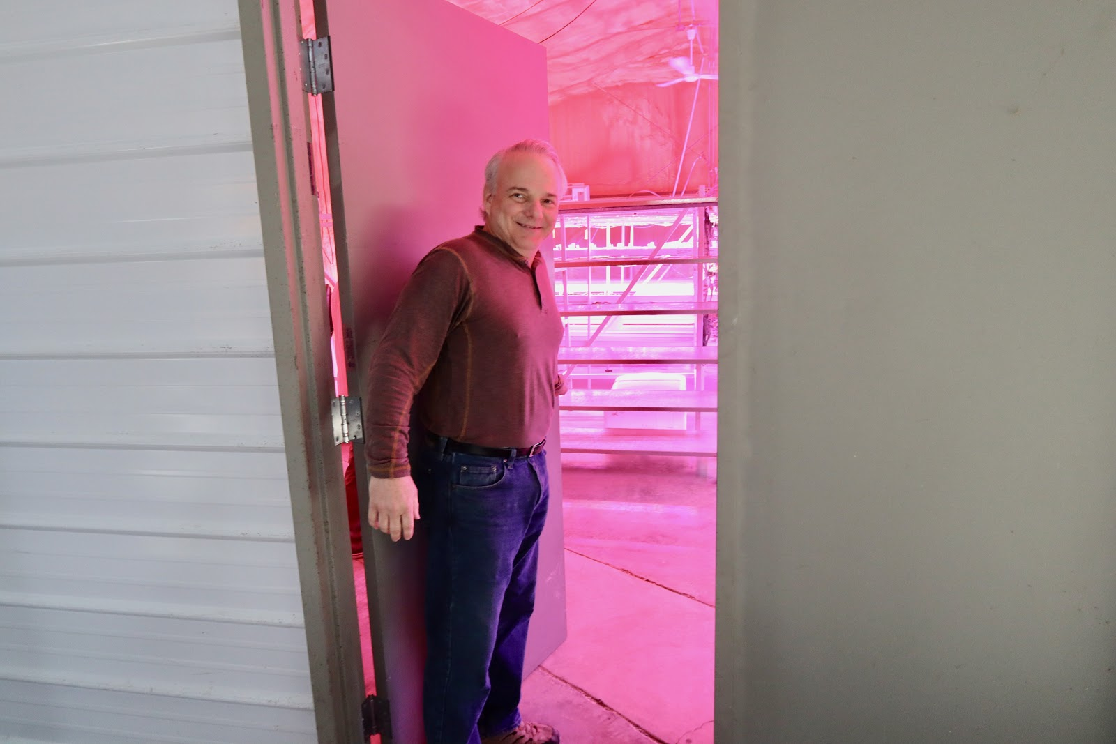 Stuart Raburn takes Bham Now on a tour of the seedling and microgreen grow room. The system is entirely automated, controlling the humidity, light and temperature by sensors. (Photo by Christine Hull for Bham Now)