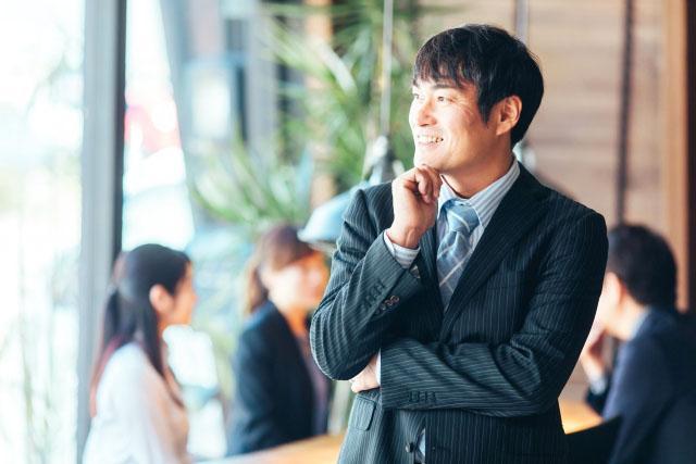 スーツを着た男性が携帯電話で話している男性  低い精度で自動的に生成された説明
