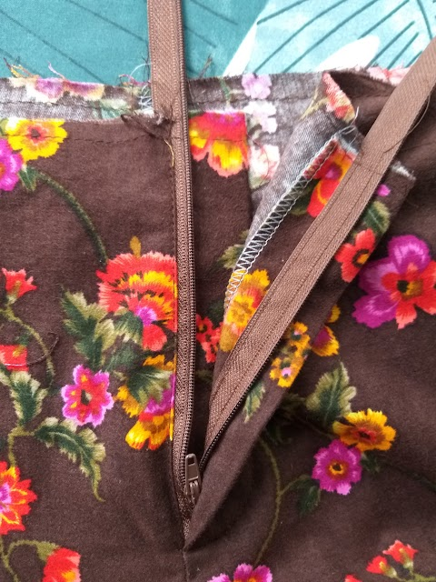 A fly front in a trouser sewn up in 70s style brown floral textured fabric. The zip is open and the waist is unfinished.