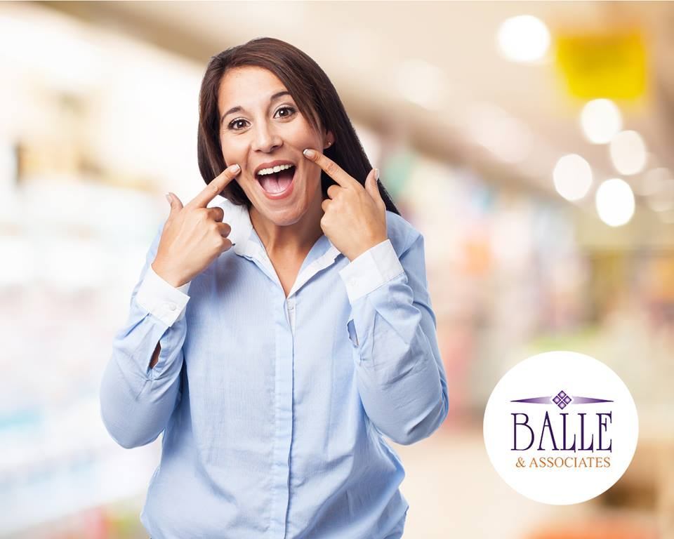 Woman pointing to her new beautiful teeth with blurred background with Balle & Associates Las Vegas Cosmetic Dentists logo on the image