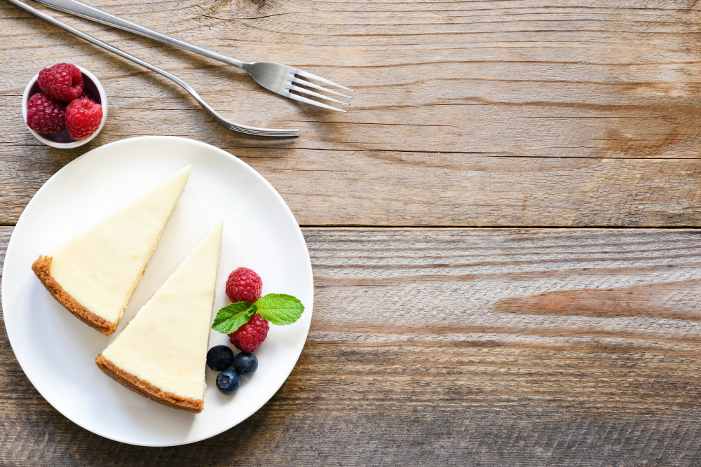 Two slices of cheesecake garnished with berries on a plate.