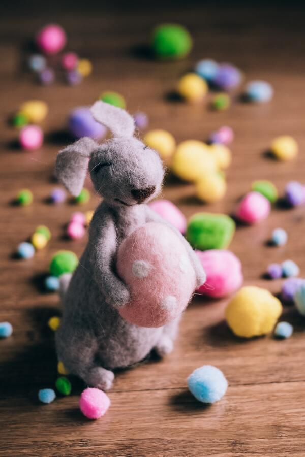 Imagem de um coelho de pelúcia segurando um ovo de páscoa rosa também de pelúcia