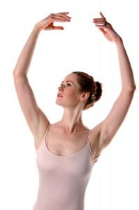 Ballerina raising arms isolated over white background