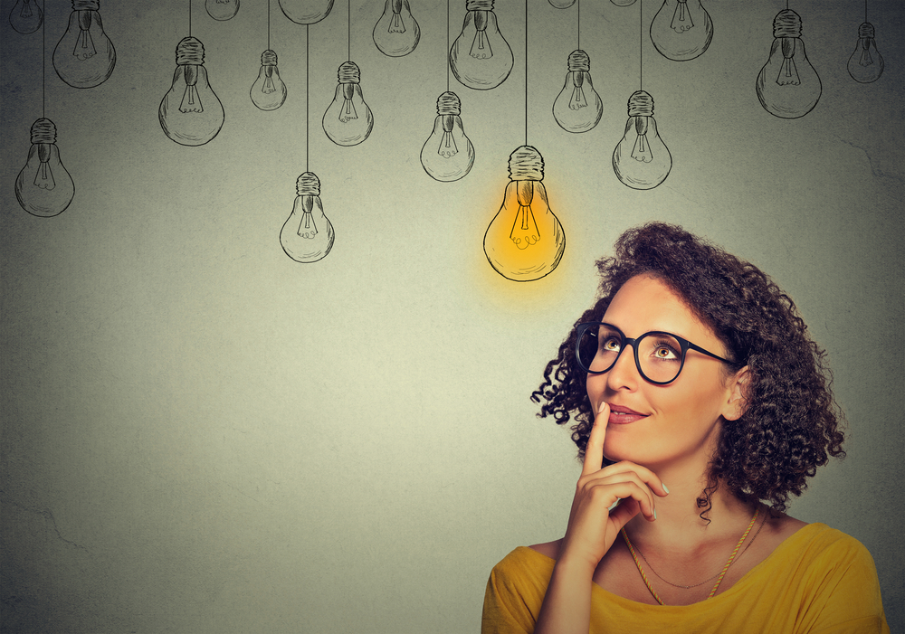 woman staring at a light bulb representing giving your employees something creative to do