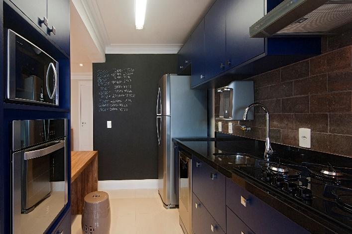 Cozinha em estilo industrial com azulejos que reproduzem pedra, armários na cor azul royal, bancada de madeira, piso branco e parede de lousa preta.