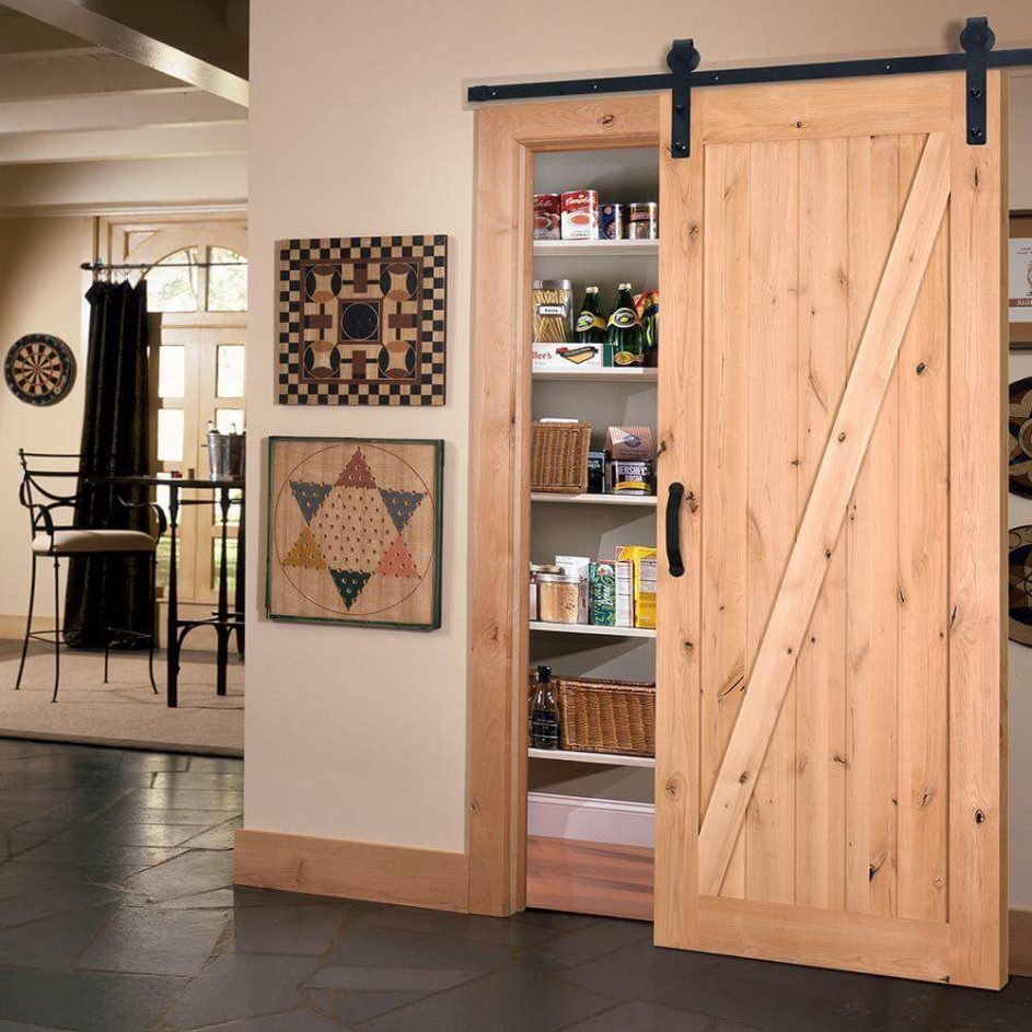 A pantry hidden by a light wood barn door