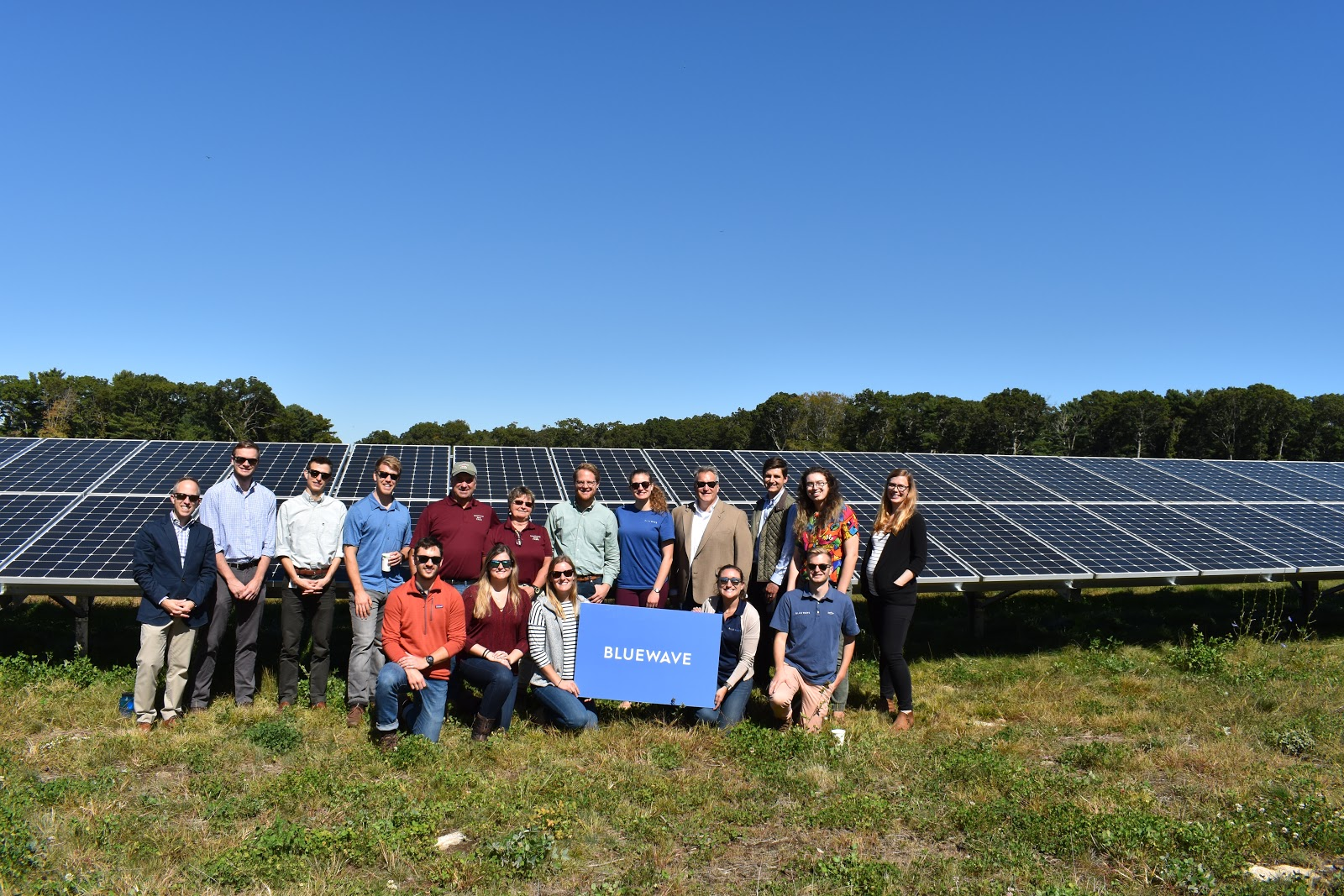 BlueWave's team gathers for a group photo next to a solar panel