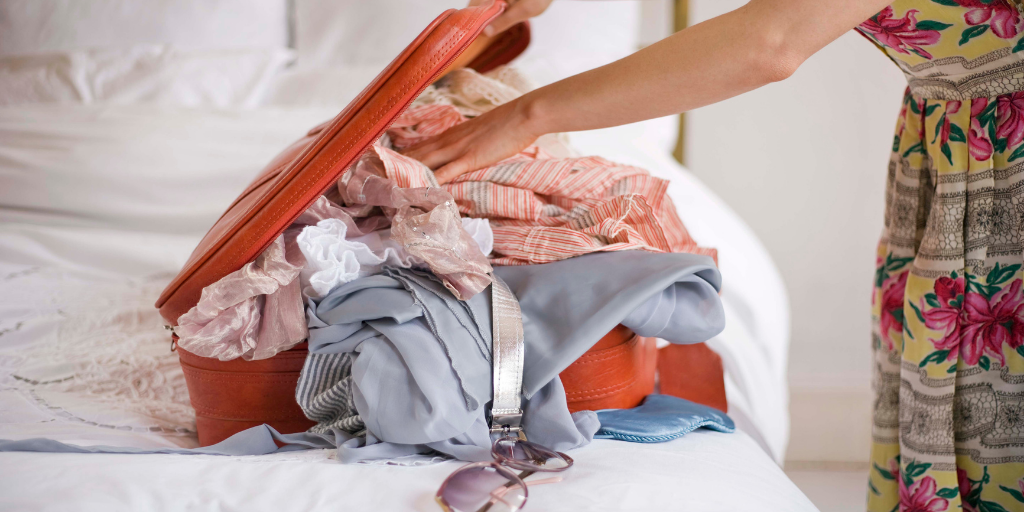 A woman packing a suitcase with lots of clothes