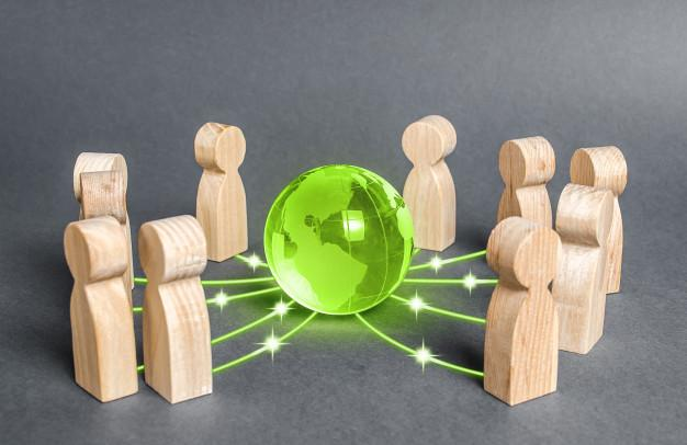 People surrounded a green globe planet earth. cooperation and collaboration of people Premium Photo