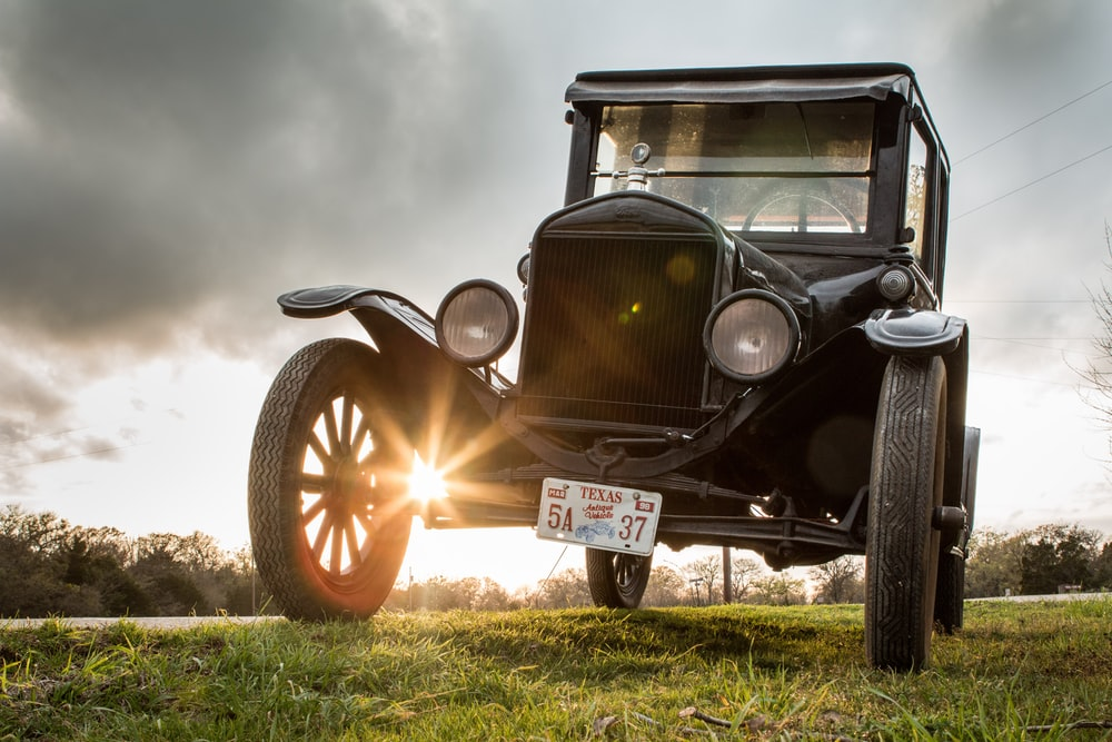 vintage black car on green grass field under cloudy sky during daytime