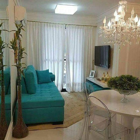 Sala com estilo mais sofisticado, sofá azul, lustre grande, cortinas longas, plantas, mesa redonda branca com cadeiras transparentes de acrílico.