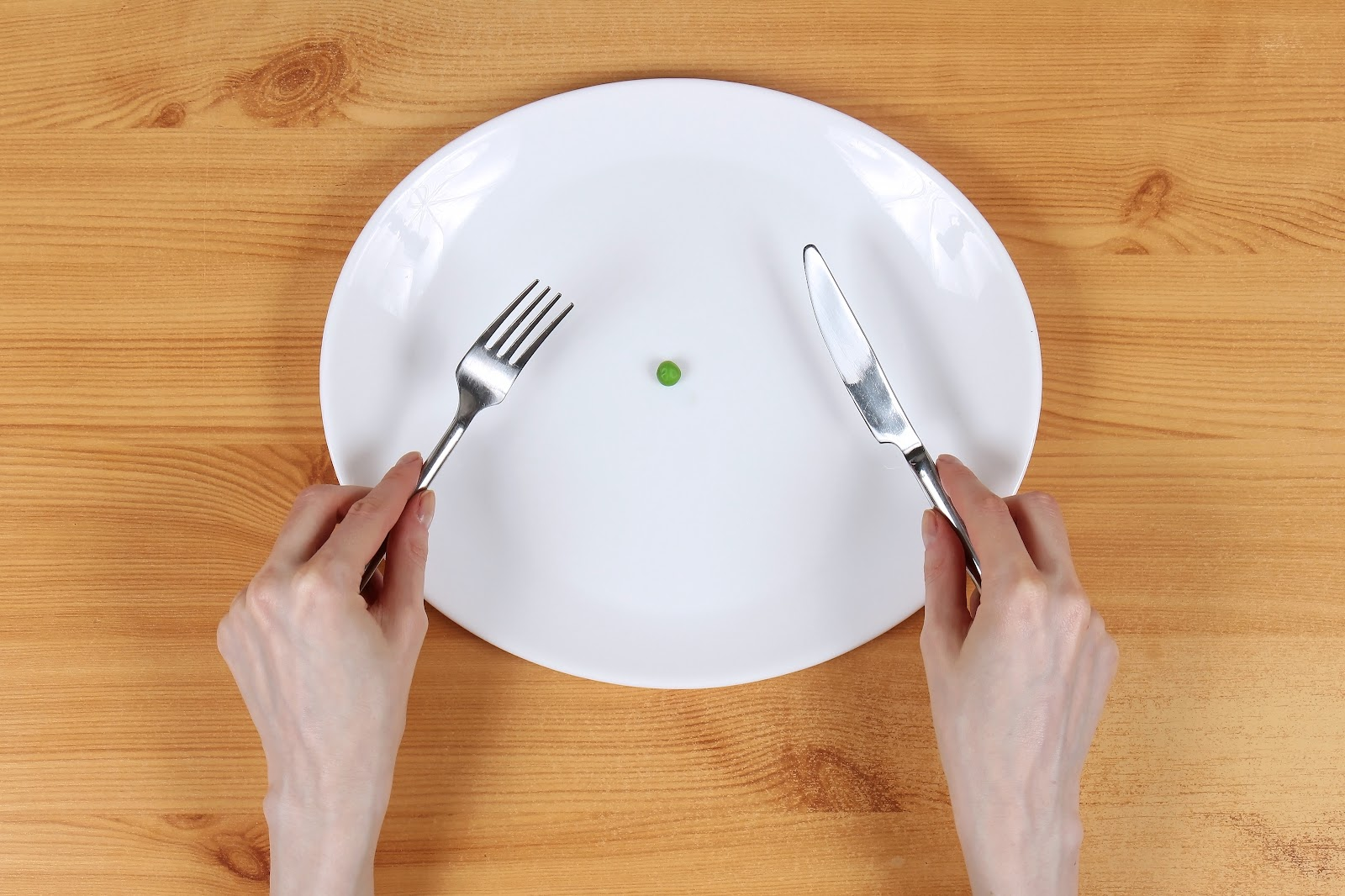 A large plate with a single pea on it