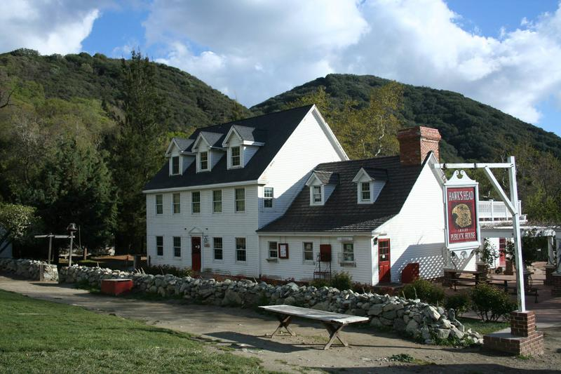 Photo of Riley's Farm, a large white farm house next to the rolling green hills.