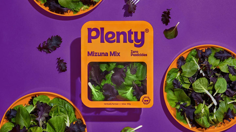 """Immagine che stimola la freschezza del prodotto insalata mista """"Mizuna Mix"""". Combina i colori viola ed arancione. Il packaging dell'insalata è circondato da 3 piatti riempiti dall'insalata mista. Fonte: agenzia &Walsh's"""
