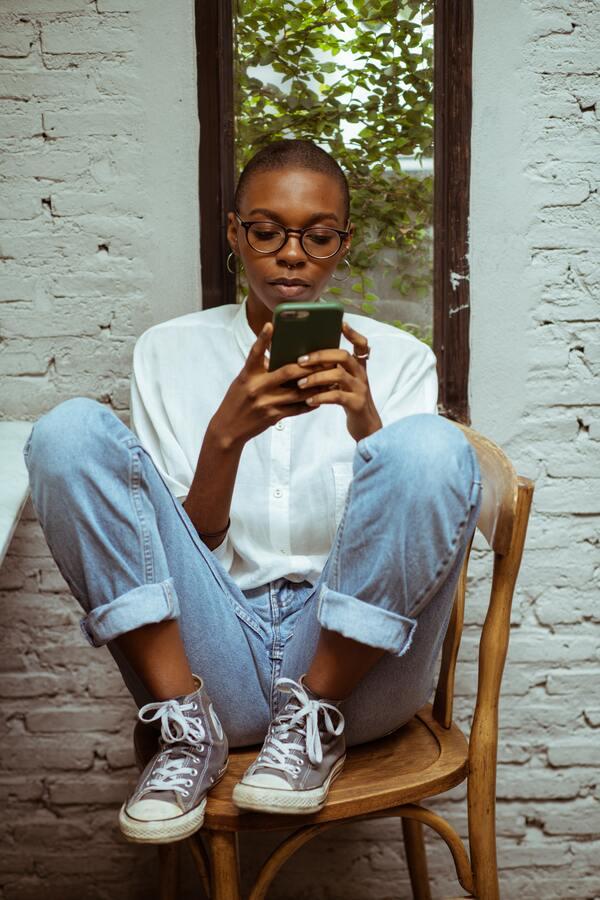 mulher negra sentada e mexendo no celular