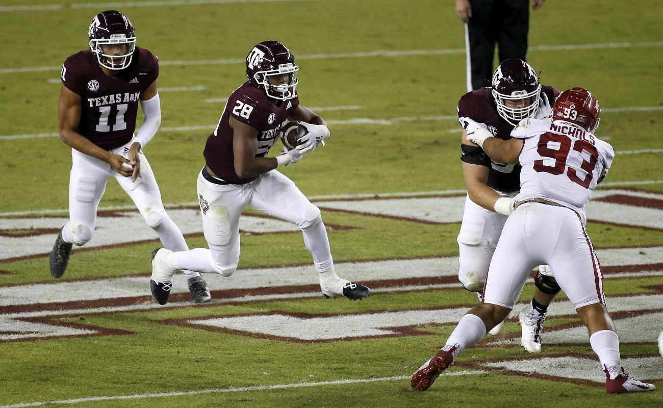 Texas A&M Aggies player Isaiah Spiller drives forward while being protected from an Arkansas Razorback player.