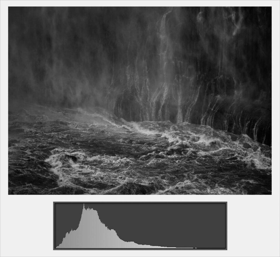 A black and white photo of a volcano erupting  Description automatically generated with low confidence