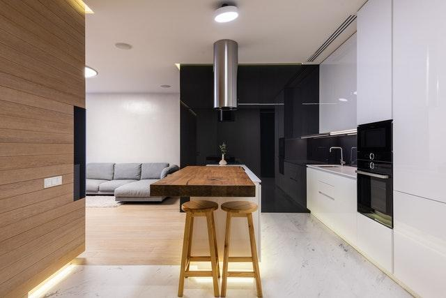 a white kitchen with a wooden dining area and a grey sofa in the living room area